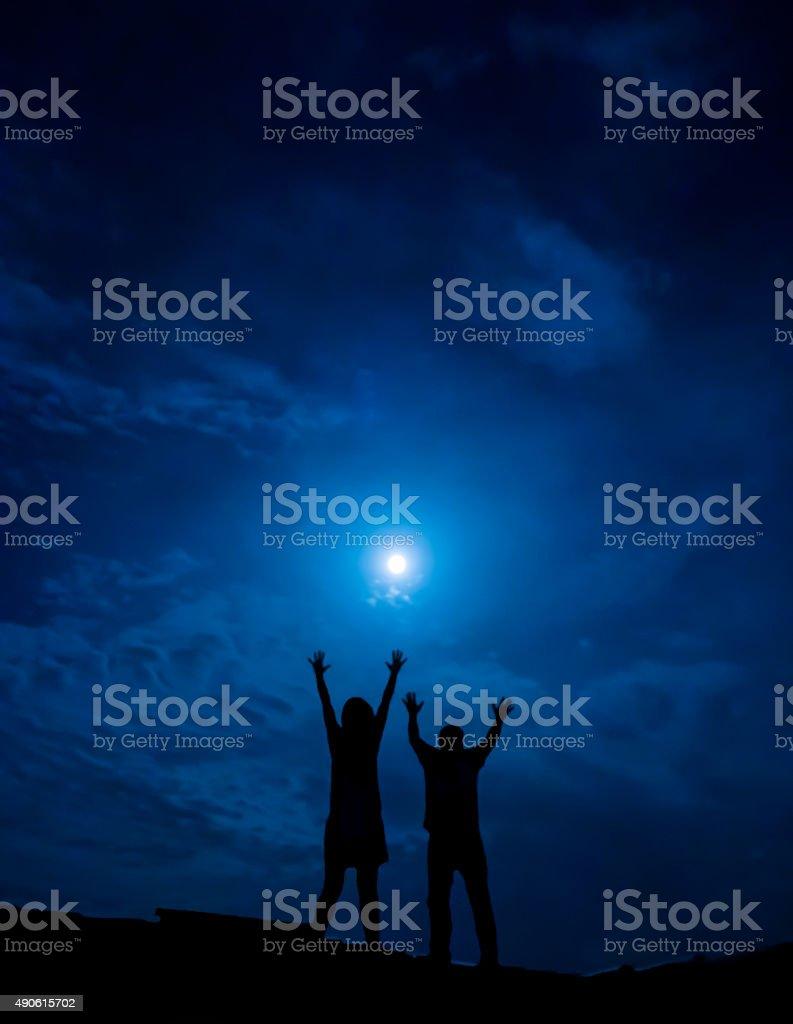 Silhueta de casal contra a lua cheia com as mãos foto royalty-free