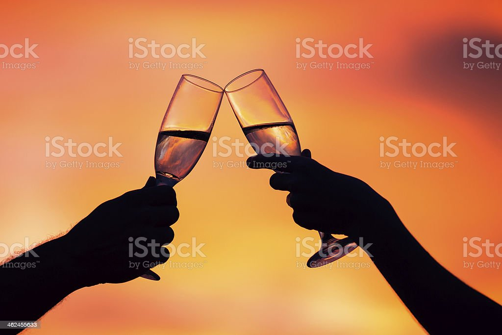 Silhouette of couple drinking champagne at sunset stock photo