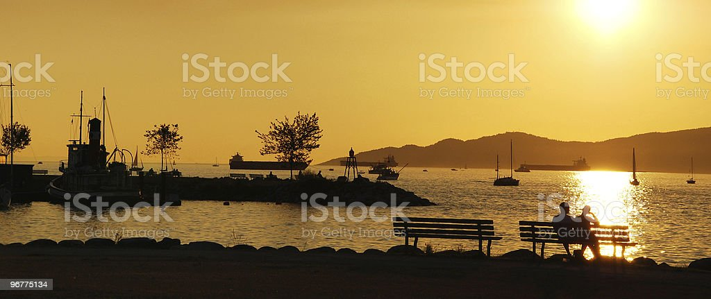 Silhouette of couple enjoy beautiful sunset view in English Bay stock photo