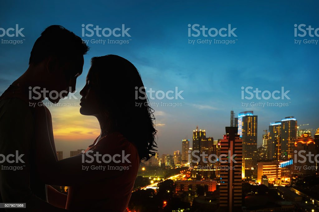 Silhouette of couple on the rooftop stock photo