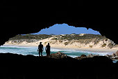 Silhouette of couple overlooking a beach in a cave