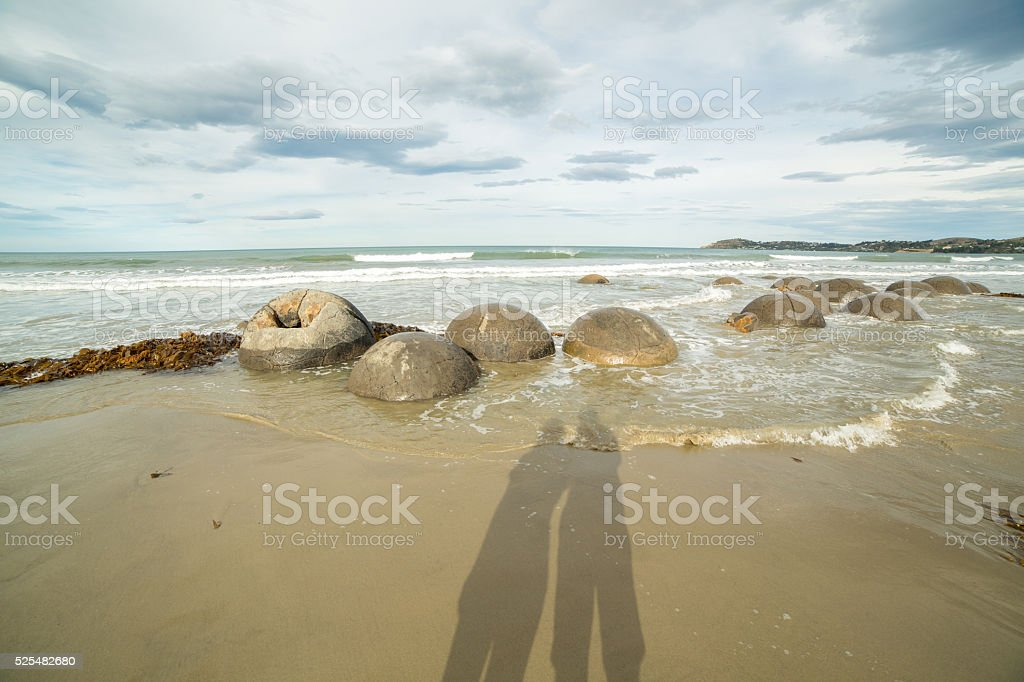 Silhouette of couple standing by the Moeraki boulders-New Zealand stock photo