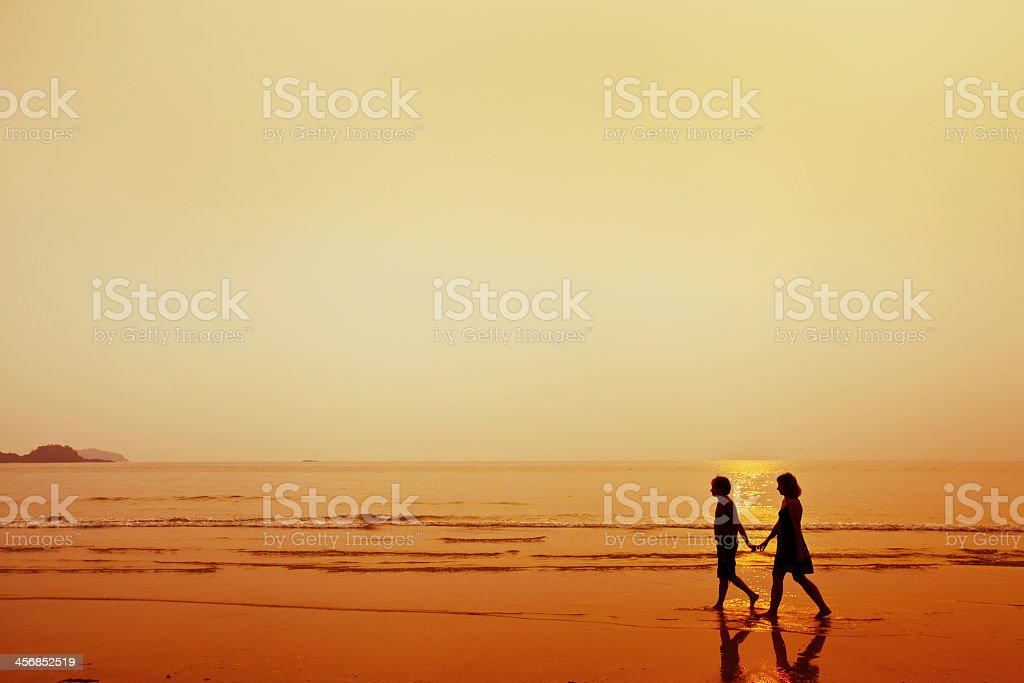 Silhouette of couple walking on the beach holding hands royalty-free stock photo