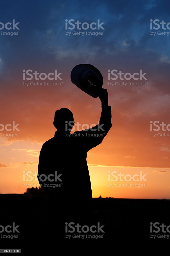 Silhouette of Cowboy Watching Sunset stock photo