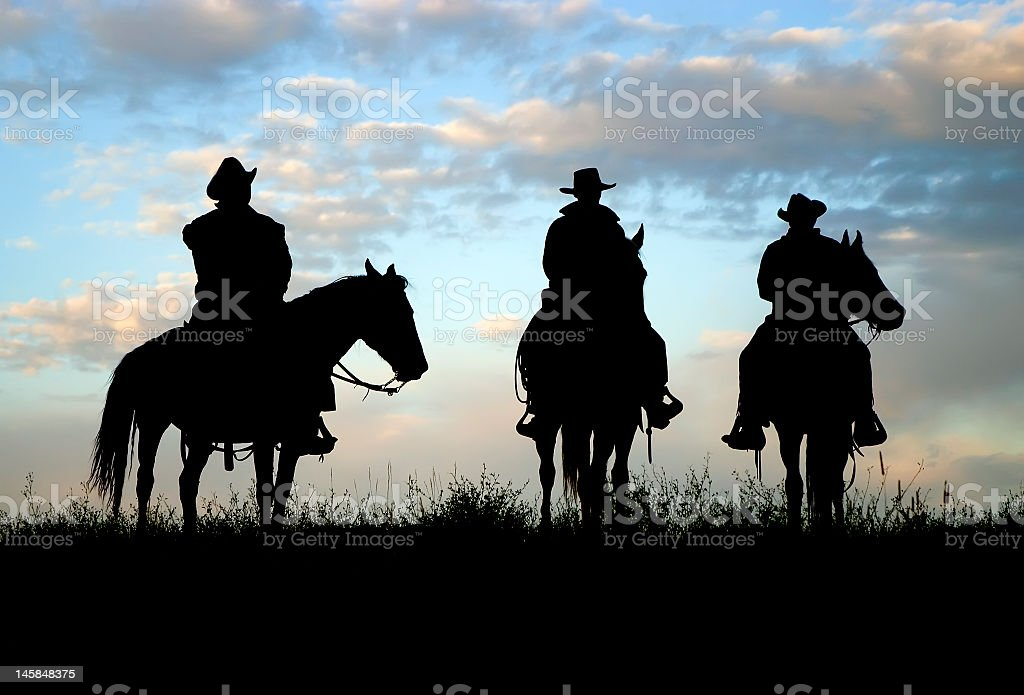 Silhouette of Cowboys on horseback stock photo