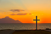 Silhouette of cross at sunrise or sunset with light rays