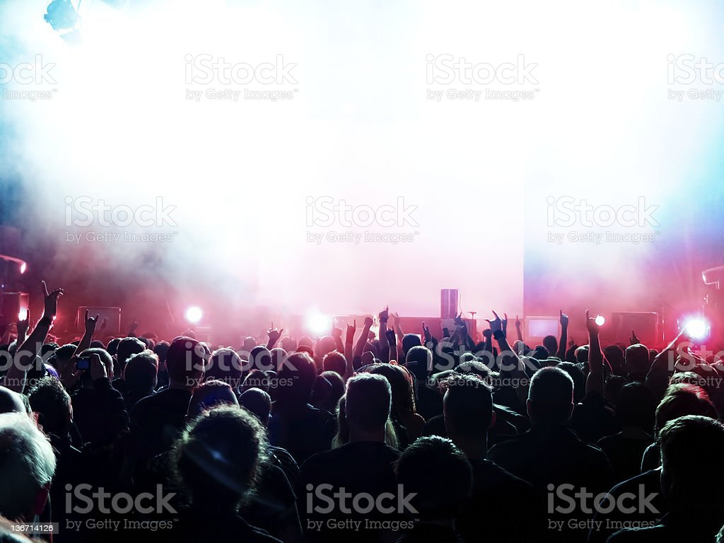Silhouette of crowd at concert with smoke and bright lights royalty-free stock photo