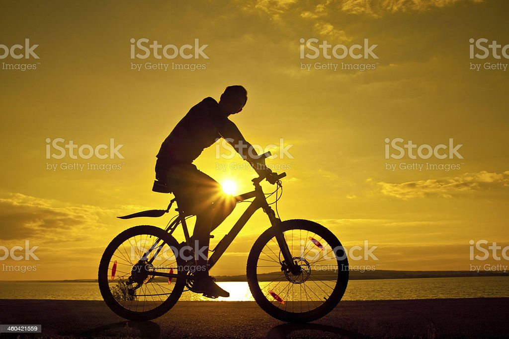 silhouette of  cyclist at sunset with reflection on water royalty-free stock photo