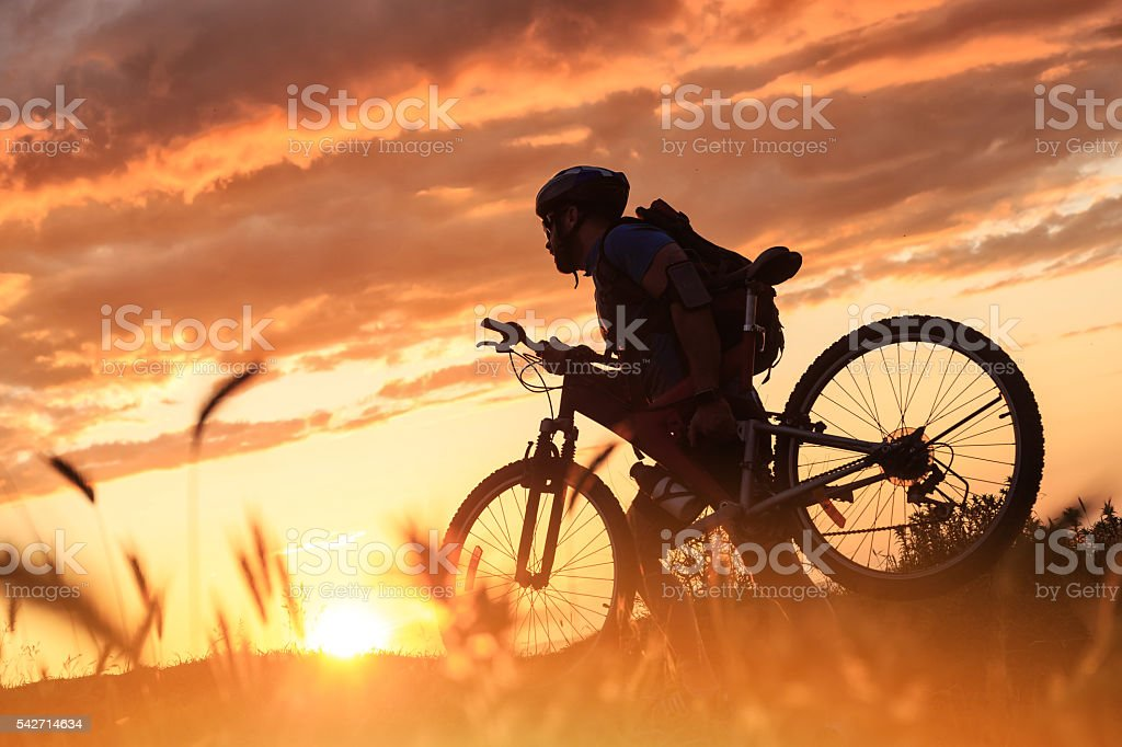 Silhouette of cyclist climbing the mountain stock photo