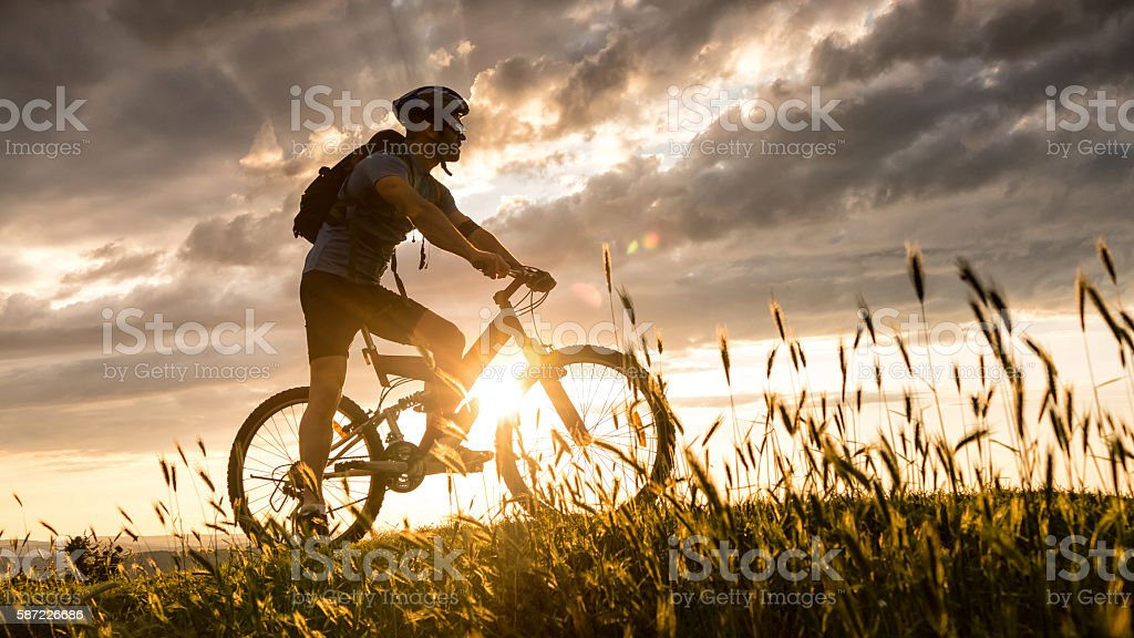 Silhouette of cyclist moving up on the mountain stock photo