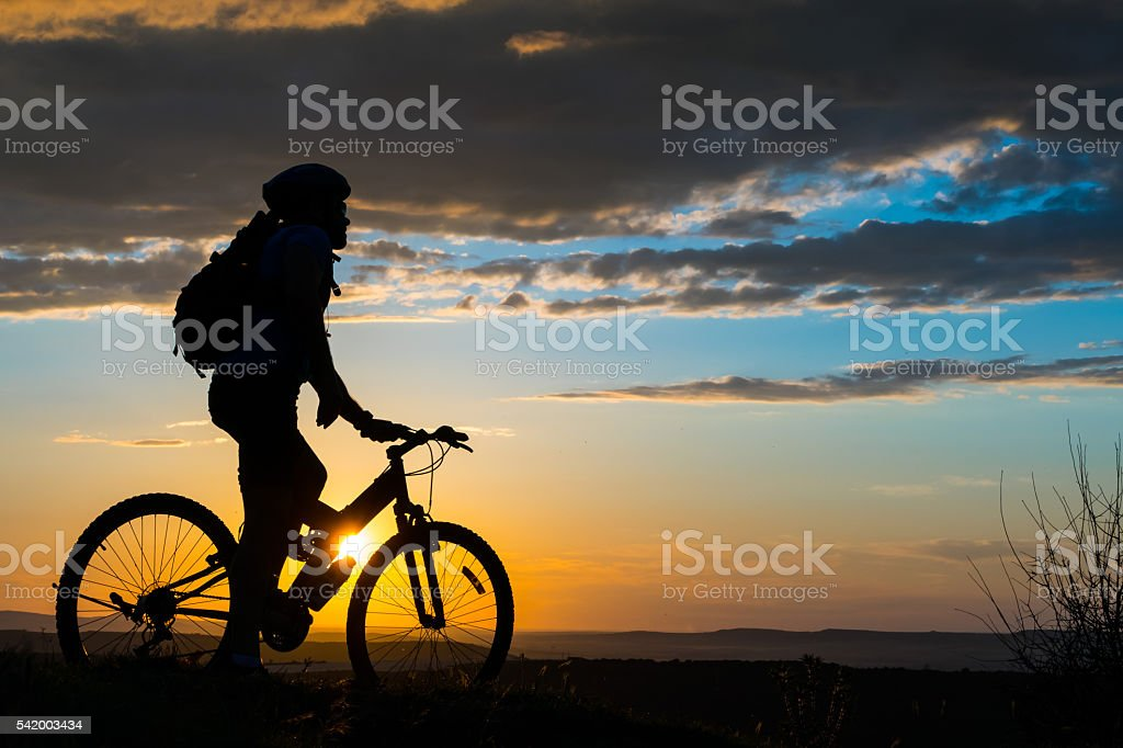 Silhouette of cyclist reaching the top of mountain stock photo