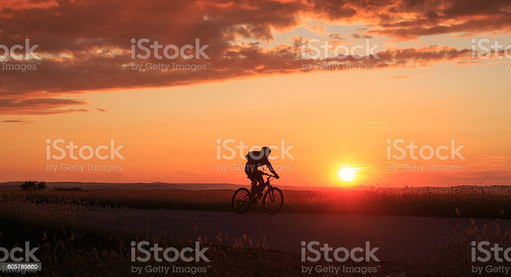 Silhouette of cyclist riding at sunset stock photo