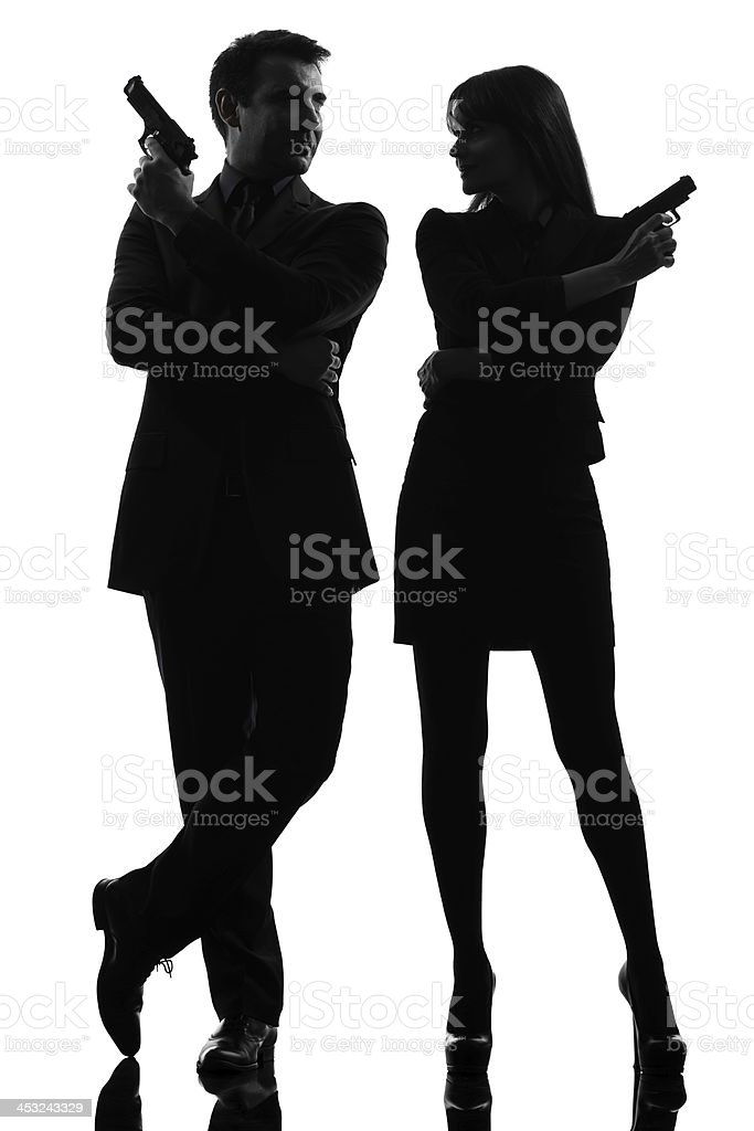 Silhouette of detective couple holding guns stock photo