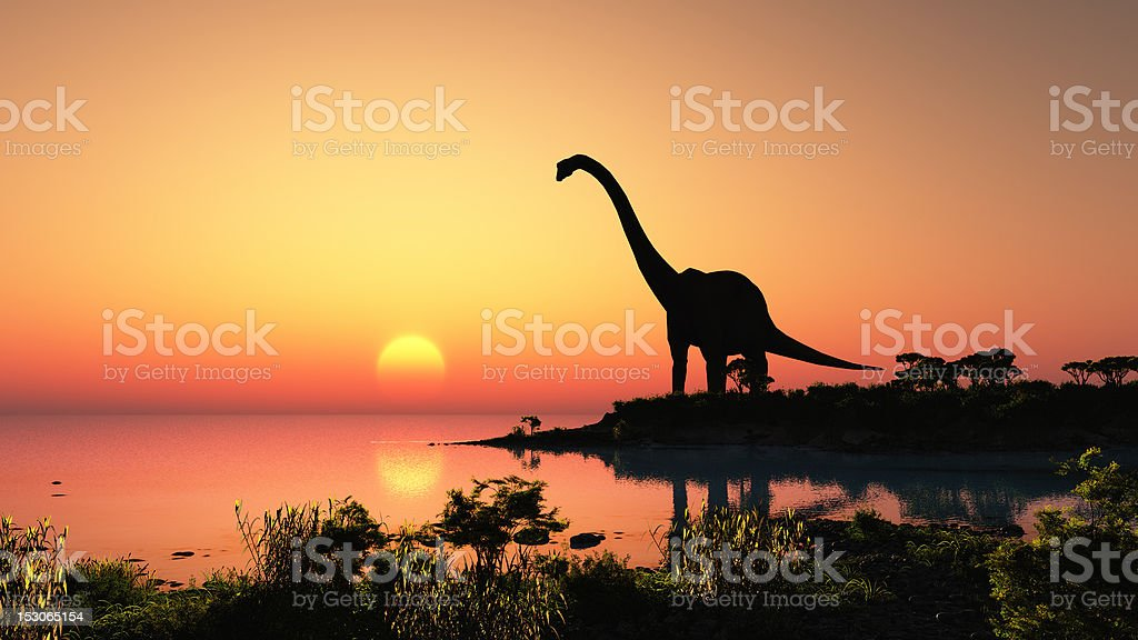 Silhouette of dinosaur at a lake at sunset stock photo