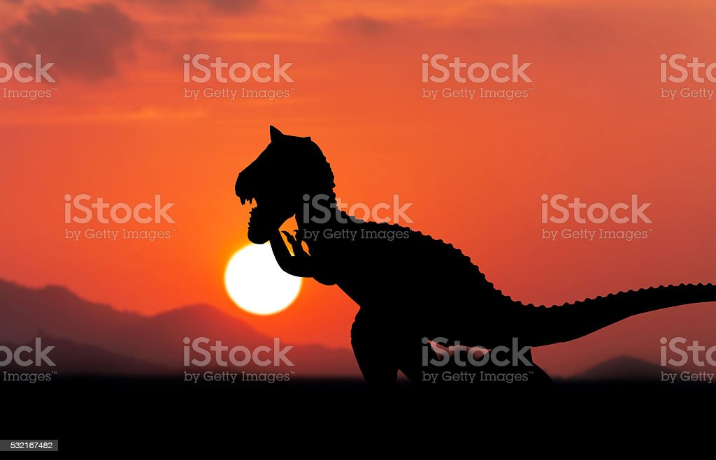 Silhouette of dinosaur sunset background stock photo