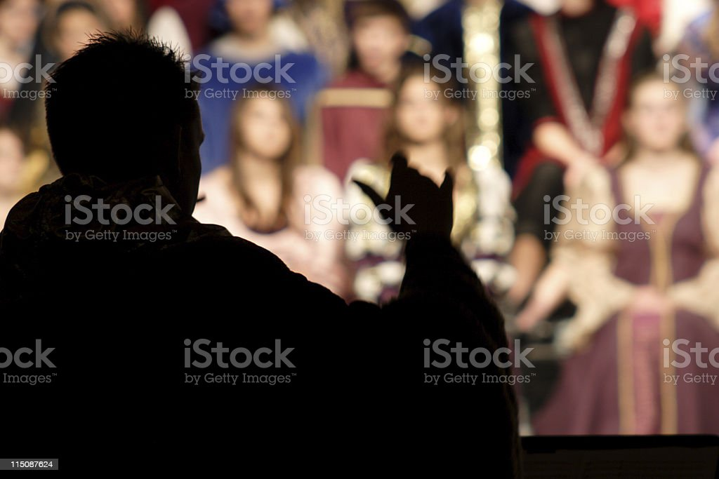 Silhouette of director of a Renaissance choir stock photo