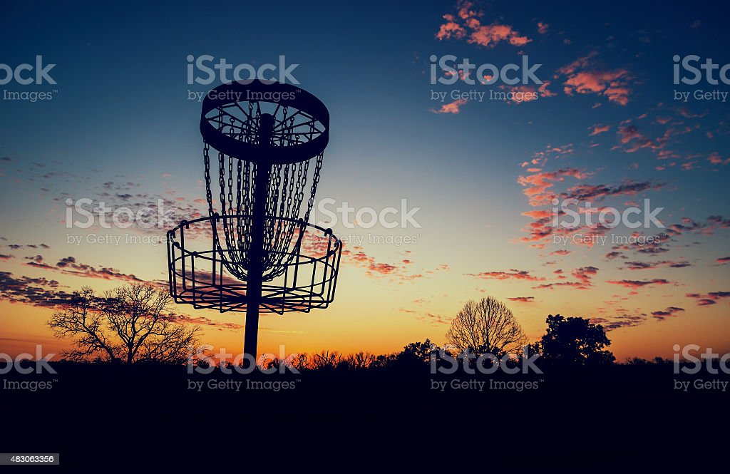 Silhouette of disc golf basket against sunset stock photo