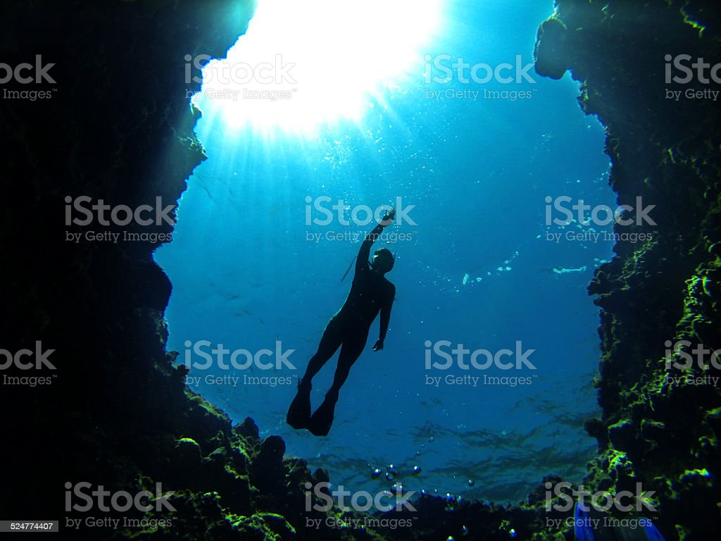 Silhouette of diver at entrance of a blue water cave stock photo