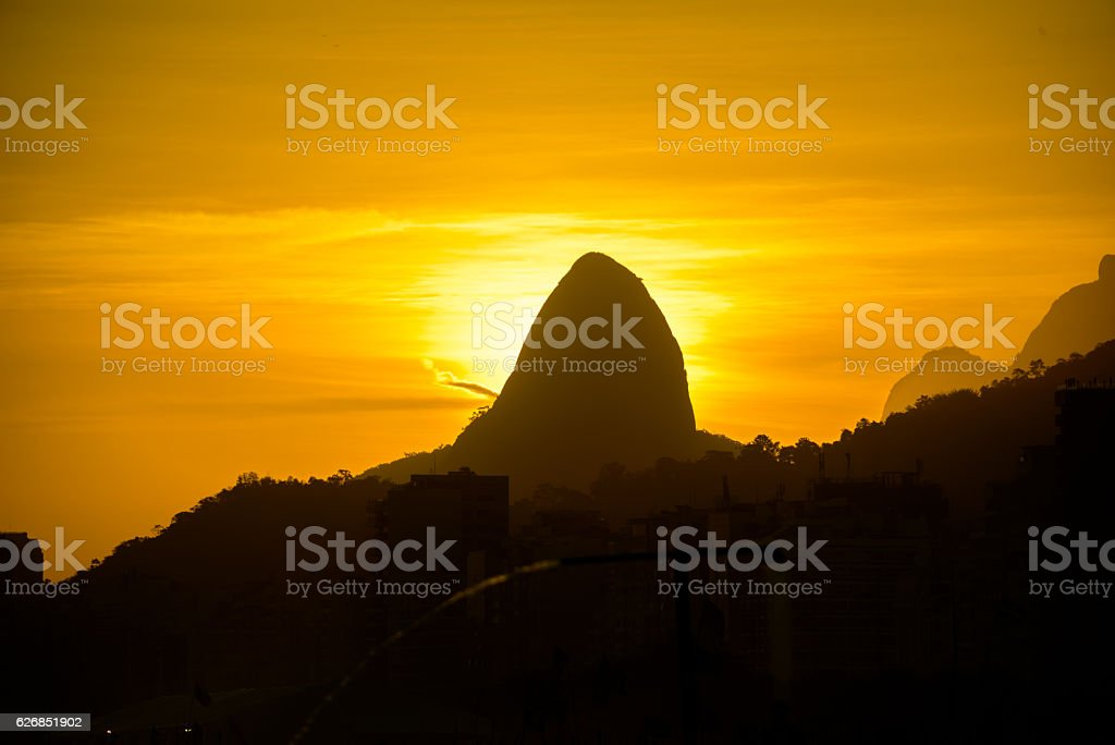 Silhouette of Dois Irmaos Mountain and sunset from Copacabana beach stock photo