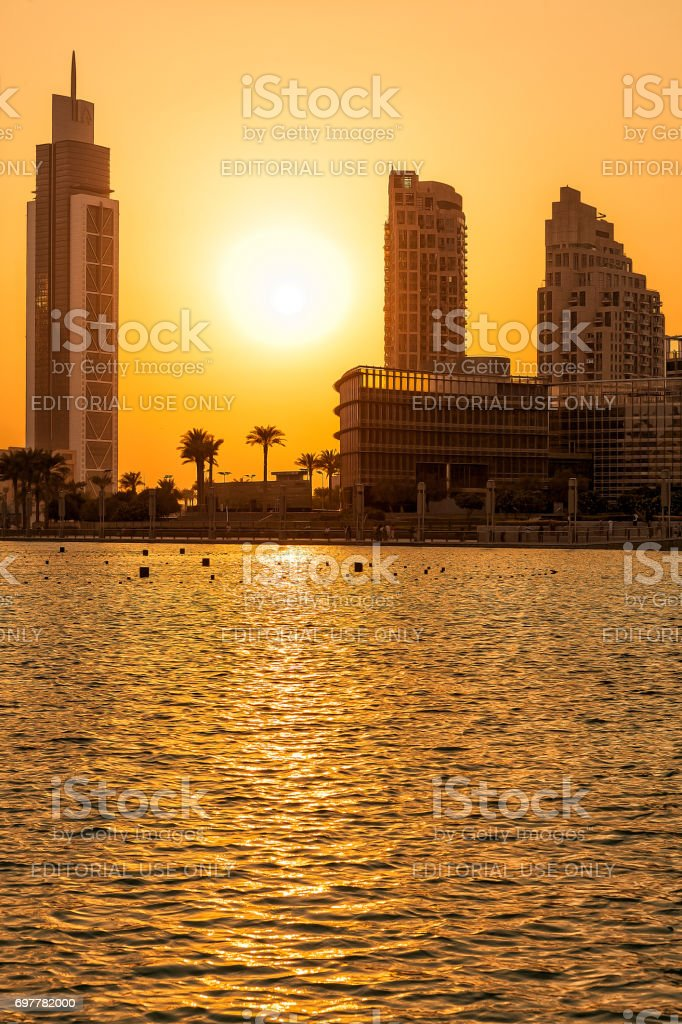 Silhouette of Dubai buildings with lake in the foreground stock photo