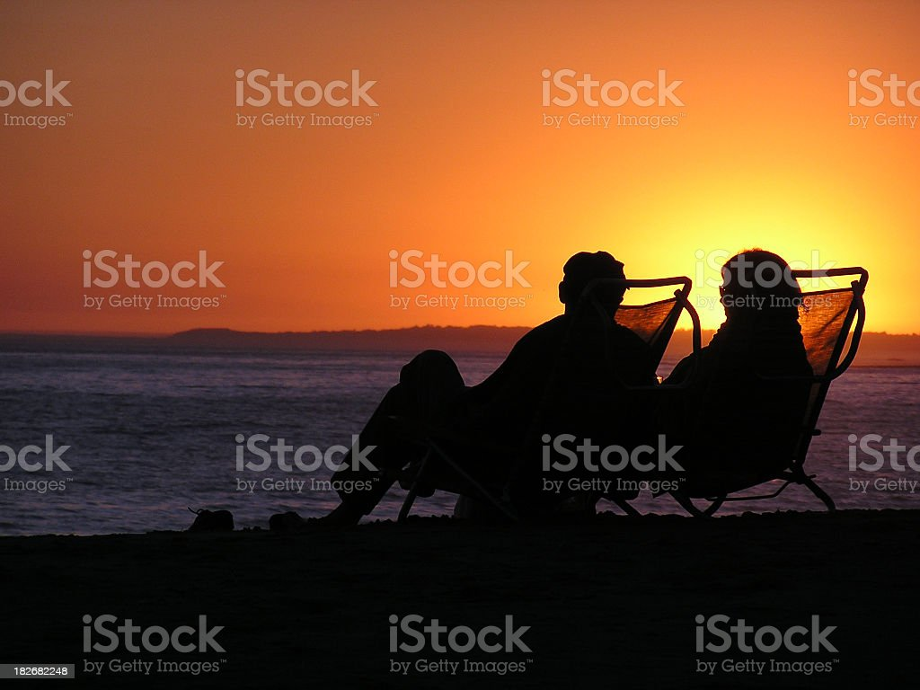 Silhouette of elderly couple sitting in deckchairs on beach stock photo