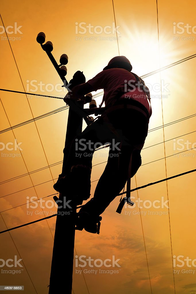 silhouette of electrician doing maintenance on power line pylon stock photo
