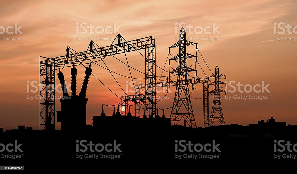 Silhouette of electricity substation at sunset stock photo