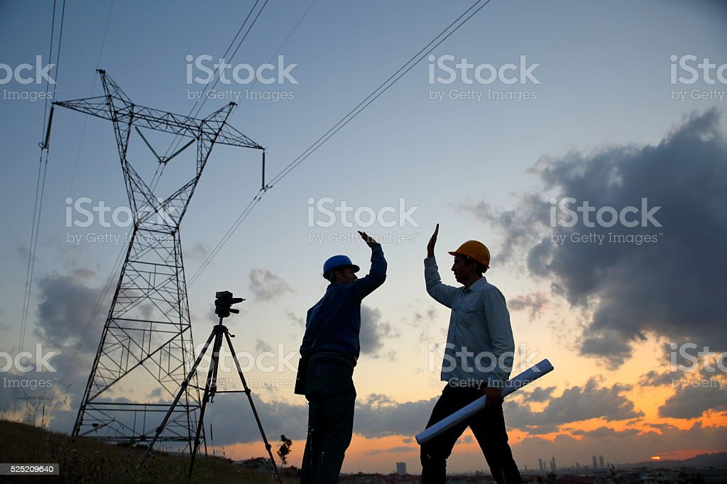 Silhouette of engineers standing at electricity station shaking hands. stock photo