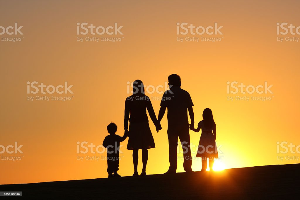 Silhouette of family of four at sunset stock photo
