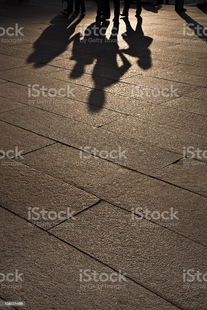 Silhouette of Family Walking on Sidewalk, Low Light. Color Image stock photo