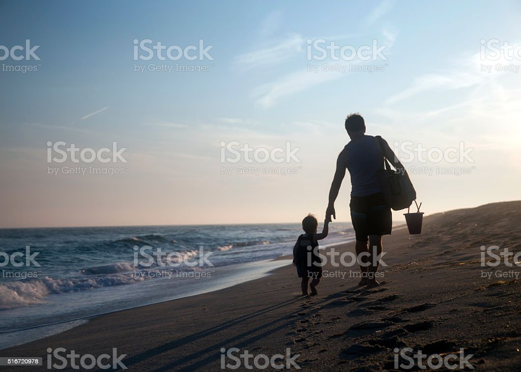 Silhouette of father and little daughter on sunset - stock photo