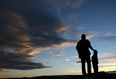Silhouette of Father and Son against sky