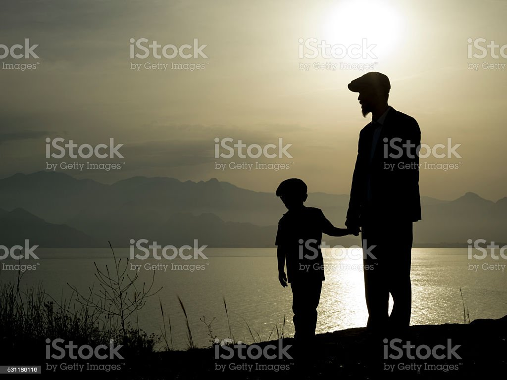 Silhouette OF Father And Son Having Chat In Sunset stock photo