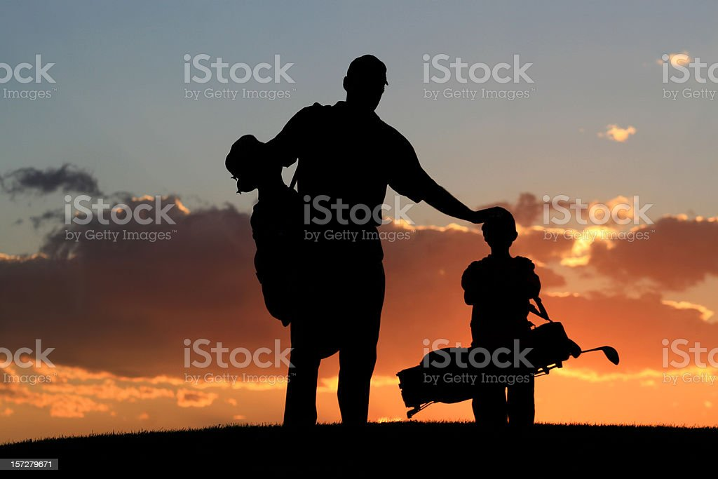 Silhouette of Father and Son on a Golf Course stock photo