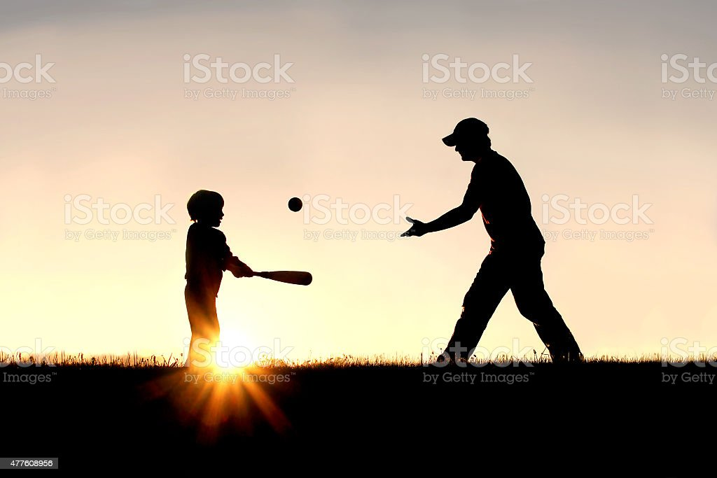Silhouette of Father and Son Playing Baseball Outside stock photo