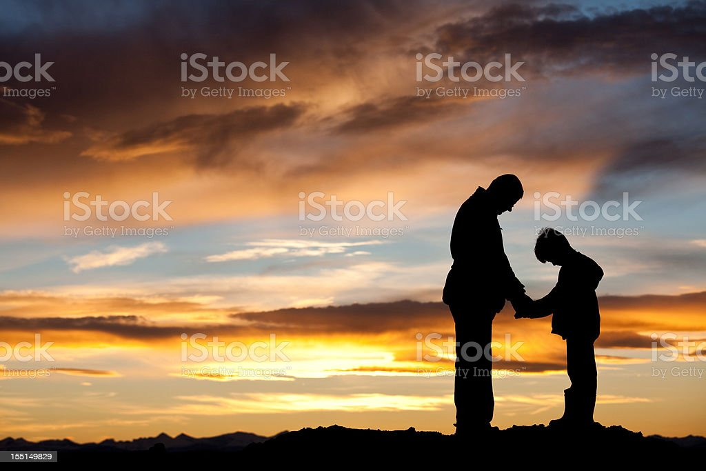 Silhouette of Father and Son Praying stock photo