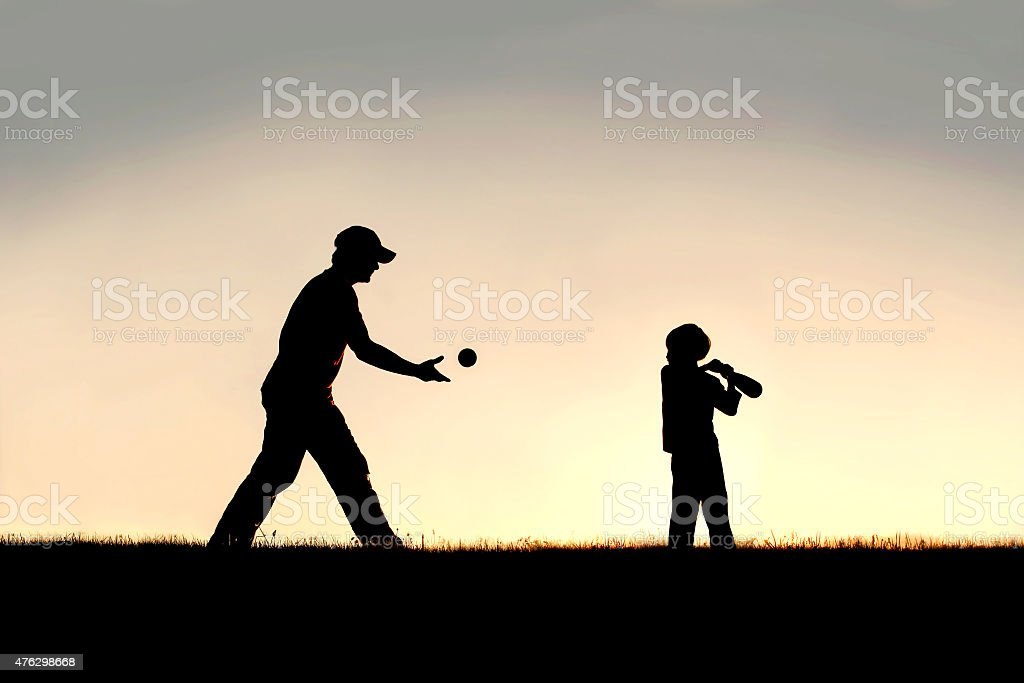 Silhouette of Father and Young Child Playing Baseball OUtside stock photo