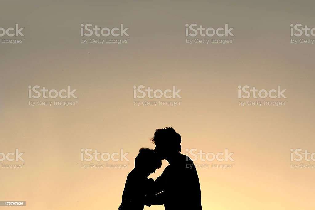 Silhouette of Father Kissing Young Child on Forehead stock photo