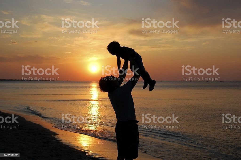 Silhouette of father lifting son in air on beach at sunset stock photo