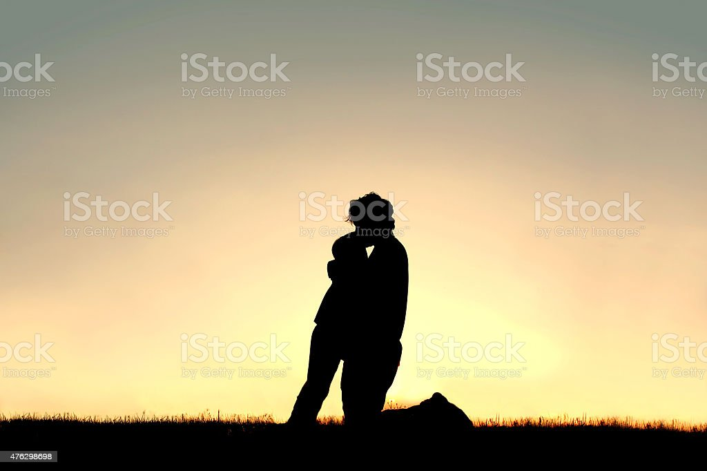Silhouette of Father Lovingly Kissing Child on Forehead at Sunse stock photo