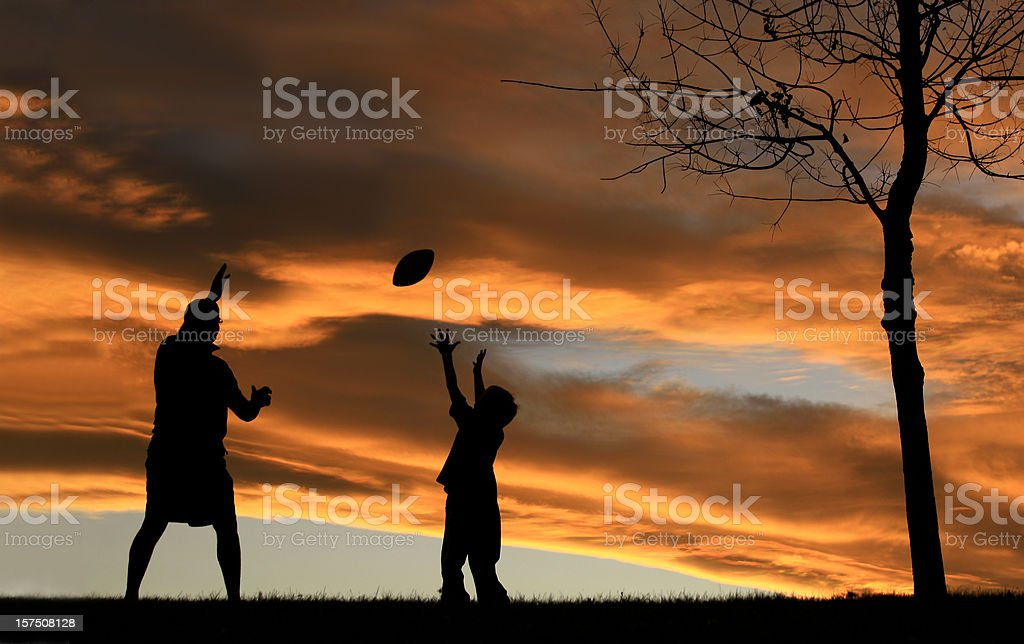 Silhouette of Father Playing Football With His Son stock photo