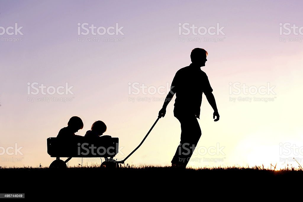 Silhouette of Father Pulling Sons in Wagon at Sunset stock photo
