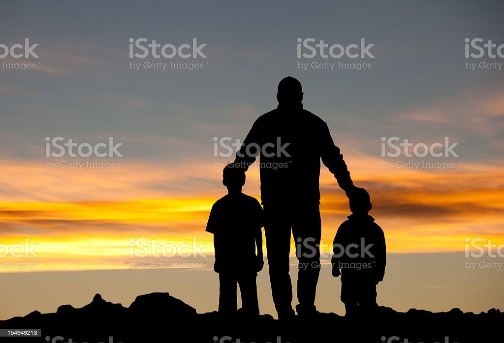 Silhouette of Father with Sons stock photo