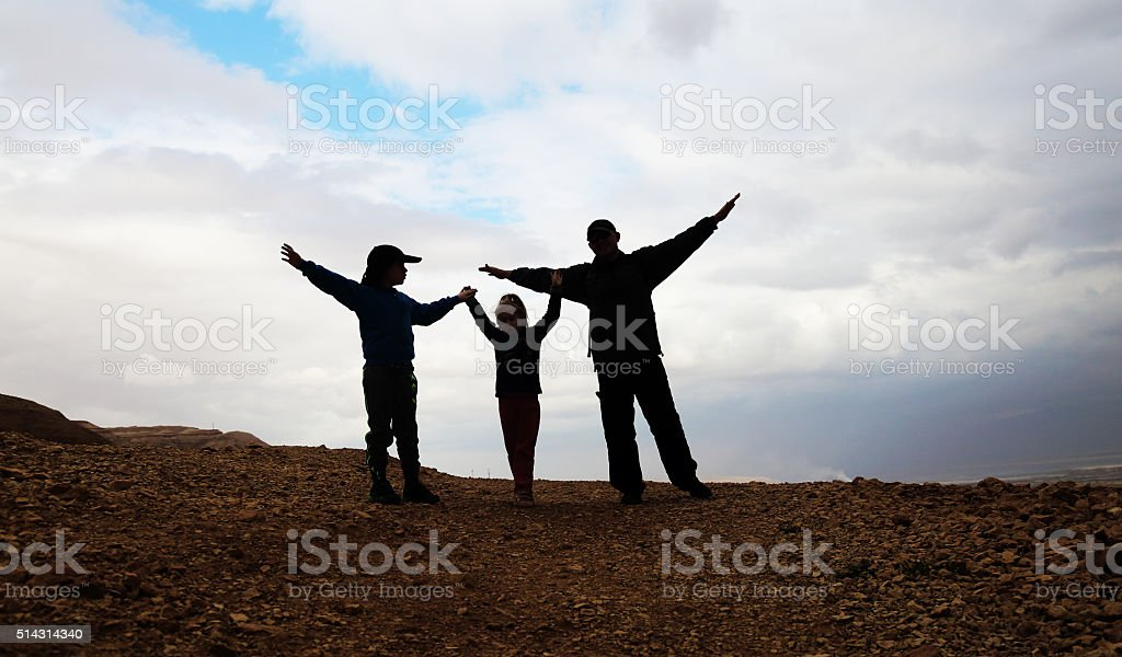 silhouette of father with two kids stock photo