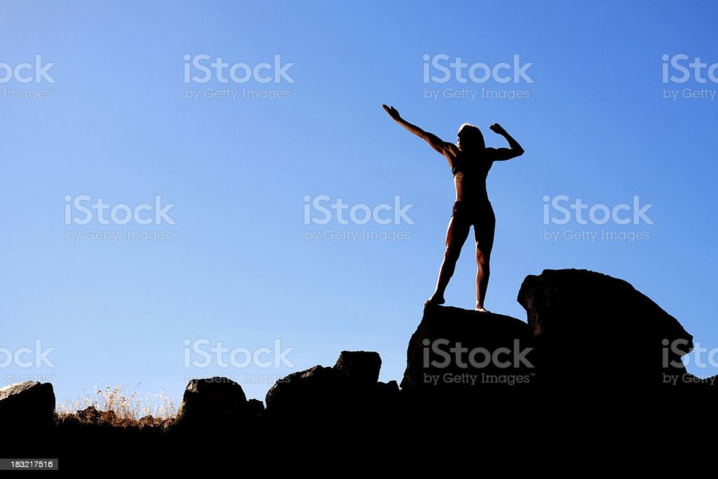 Silhouette of Female Bodybuilder on Rocks with Sky Background royalty-free stock photo