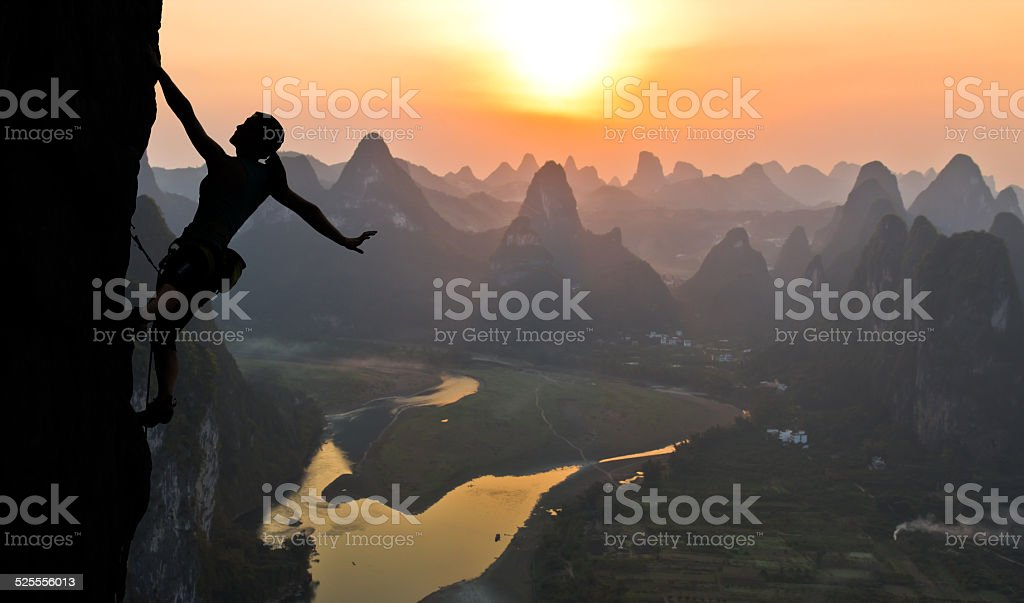 Silhouette of female climber on the Chinese landscape stock photo