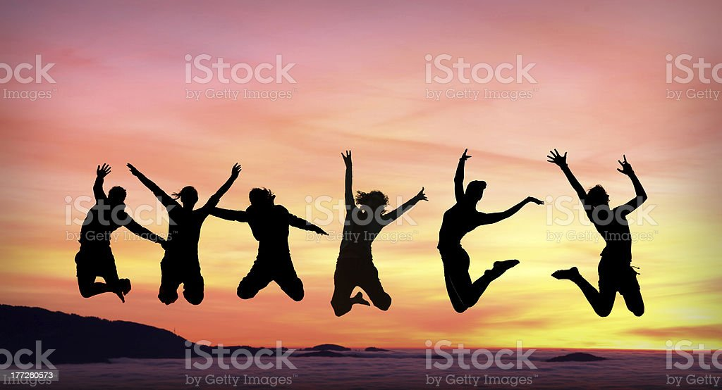 silhouette of female friends jumping in sunset stock photo
