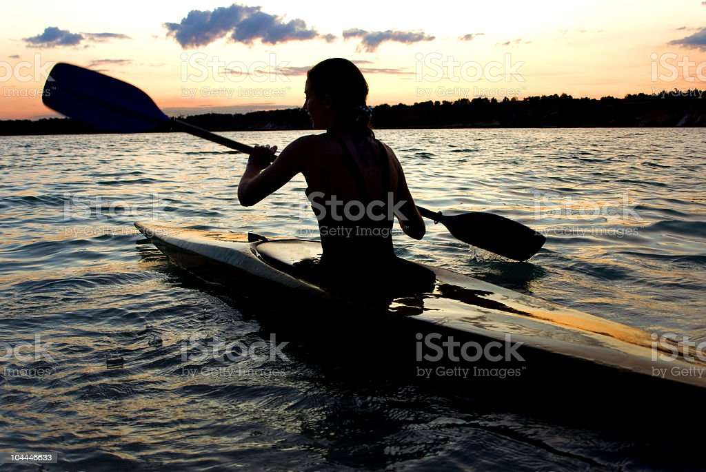 Silhouette of female kayaker in the middle of a lake stock photo