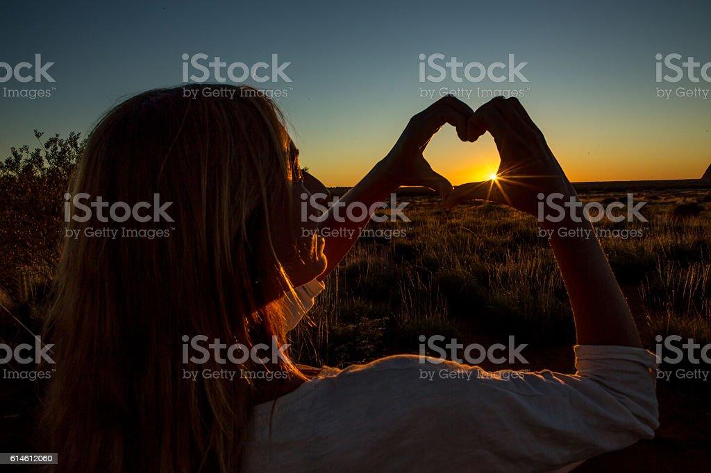 Silhouette of female making heart shape finger frame on sunset stock photo