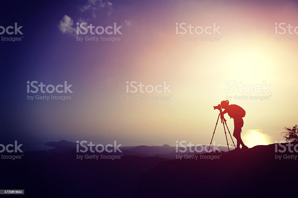 Silhouette of female photographer on top of a hill at sunset stock photo